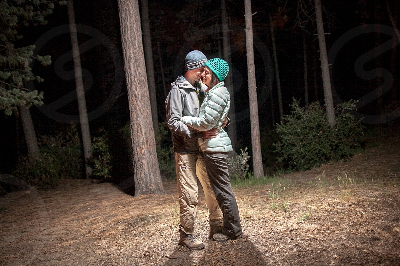 Love in the great outdoors. Cold jackets trees trail winter gortex couple relationship team beanies youth night dark evening photo