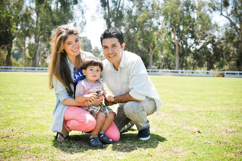 family of three sitting on green grass field surrounded by green leaf trees photo