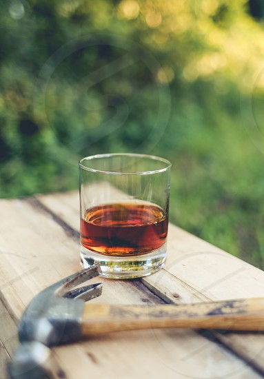 clear glass cup with red wine beside brown handle claw hammer on top of brown wooden table photo
