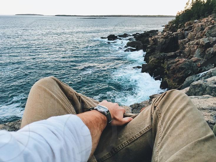man in brown denim pants sitting on rocky beach photo