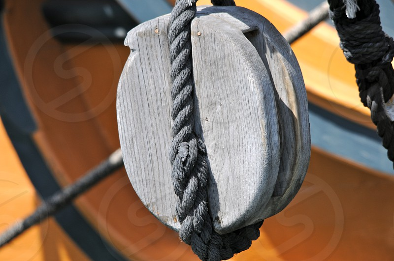 Old pulley on a wooden sailboat.   photo