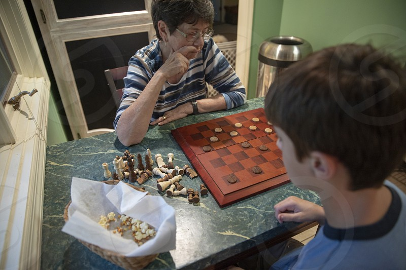 Grandmother and grandson play board game inside photo