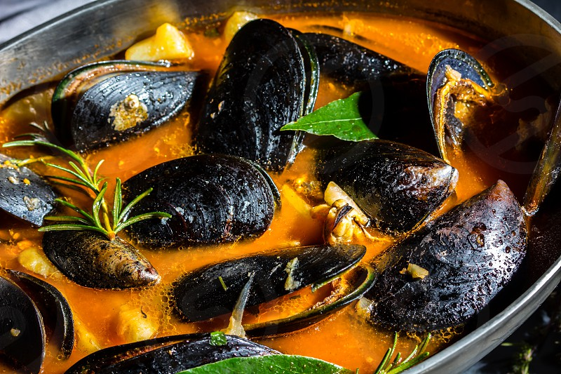 Seafood mussels tomato soup in metal pot gray background photo