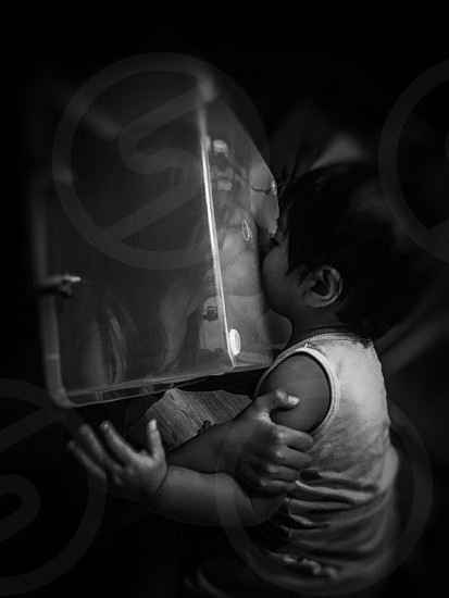 grayscale photo of woman with translucent box in head kissing toddler wearing sleeveless tank top photo