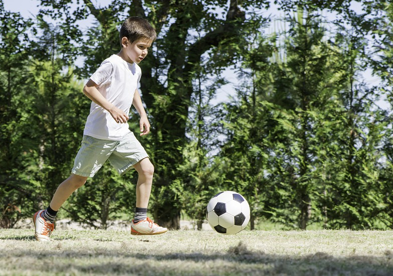 Child playing football in a stadium. Trees on the background photo