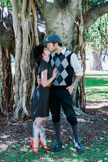 couple kissing on green grass under green tall tree during daytime photo