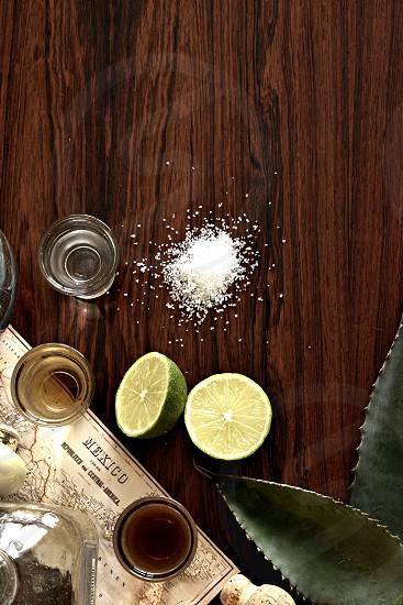 Tequila limes salt dark grain table agave leaves Mexico map silver reposado anejo bottles corks copy space. photo