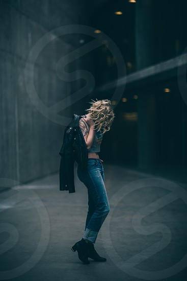 Girl standing jacket jeans boots hipster looking down fashion editorial crop top tattoo dark photo