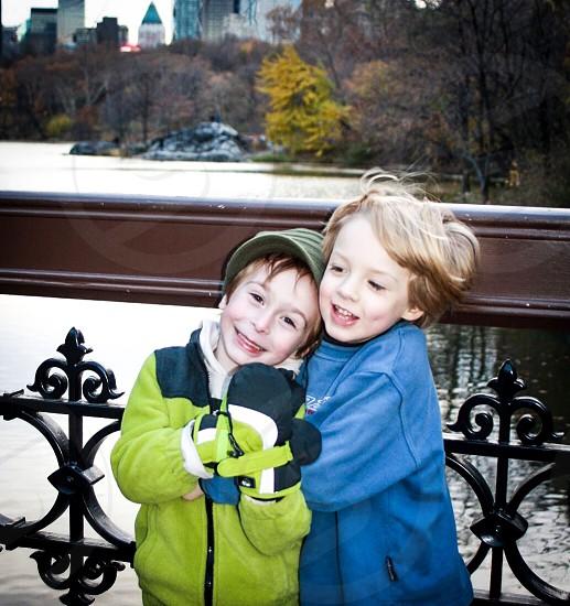 Boys buddies friends lake bridge winter cold huddle to stay warm park New York City Central Park colors photo