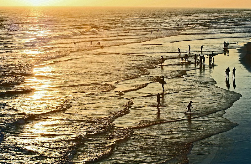 Aerial view of silhouettes of people wading in the ocean at the golden hour. photo