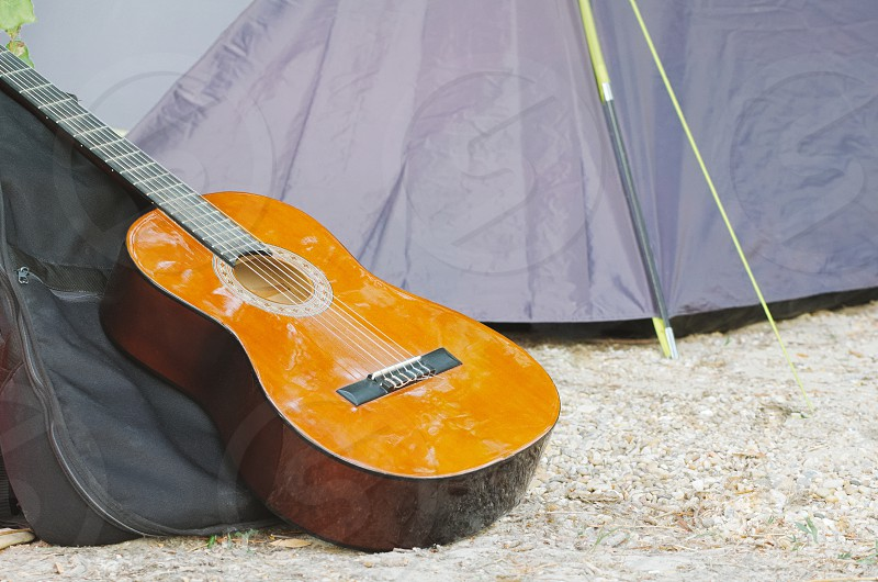 Guitar and Tent on Pebble Ground Outdoor Closeup photo