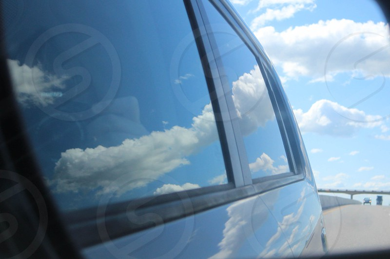 Reflection of the blue sky and clouds on car window and side of car as reflected from review mirror. photo