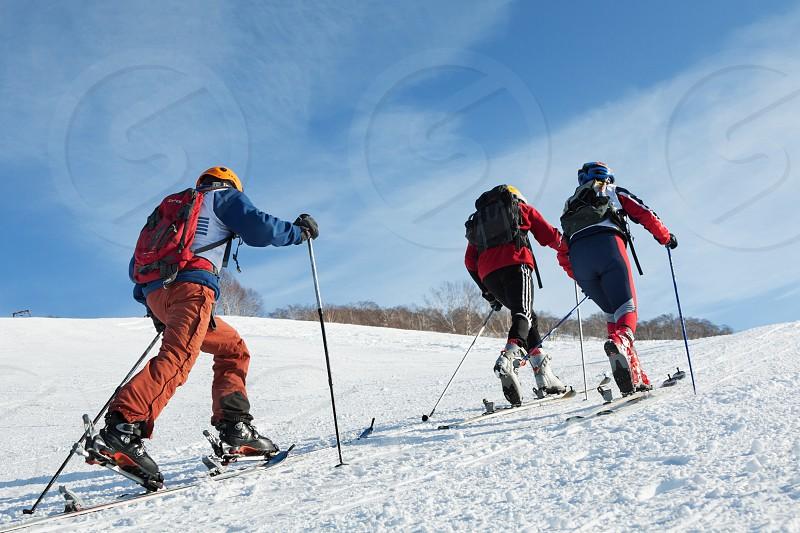 KRASNAYA SOPKA PETROPAVLOVSK-KAMCHATSKY KAMCHATKA RUSSIA - FEB 4 2012: Group of ski-mountaineers climb the mountain on skis. Ski-mountaineering competitions - Cup Petropavlovsk-Kamchatsky City. photo
