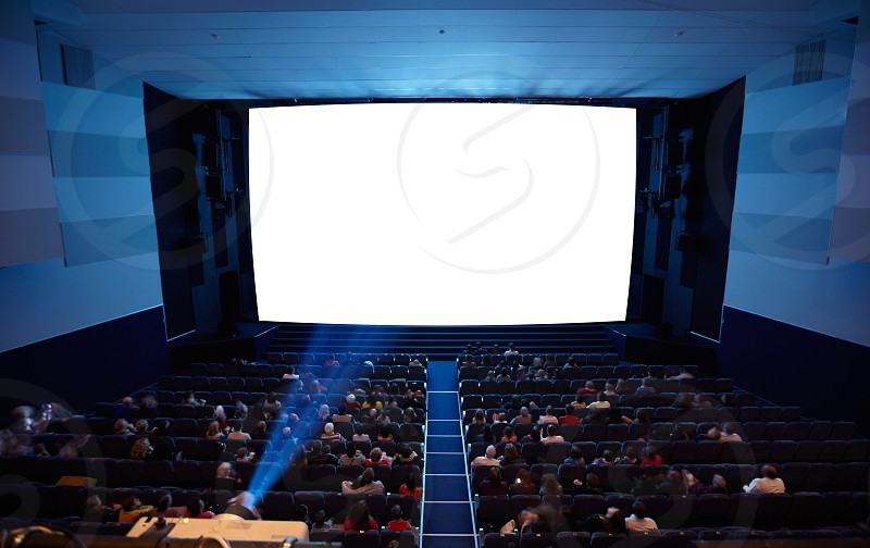 Cinema auditorium with people in chairs watching movie. Light of projector. High angle. Frontal view. Ready for adding your own picture. photo