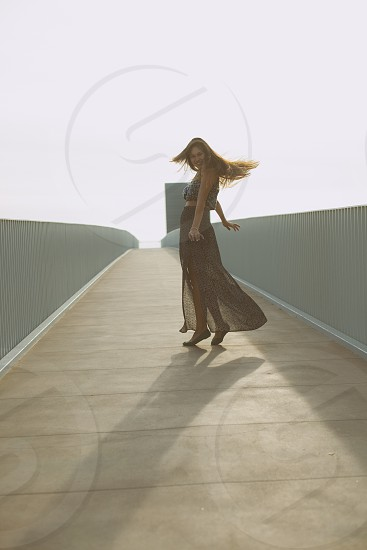 woman with long brown hair twirling on gray walkway gated photo