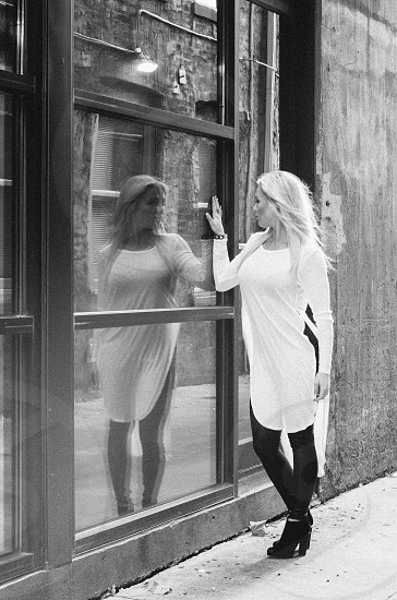 woman in white scoop neck long sleeved dress touching the glass wall in grayscale photo photo