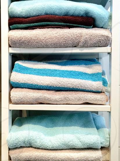 white towel rack full of towels photo