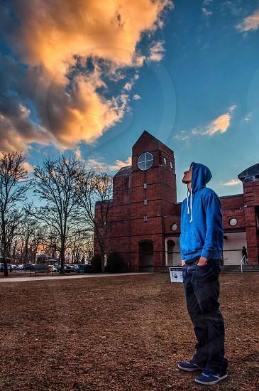 man in blue hoodie staring at sky photo
