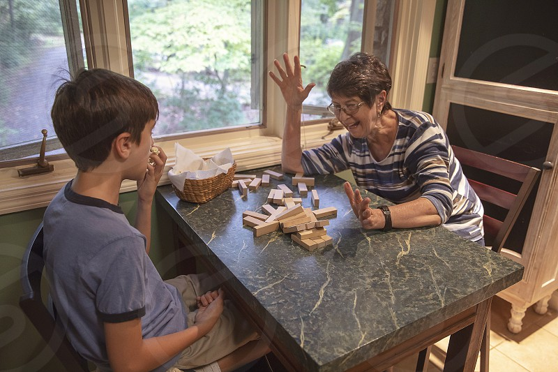 Grandmother and grandson play board game indoors photo