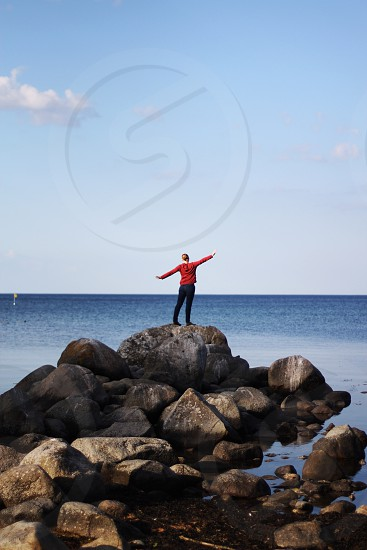 person standing on rocks near water photo