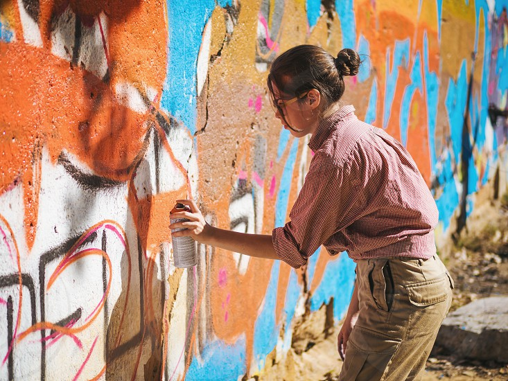 Beautiful Young Girl making a colorful graffiti with aerosol spray on urban street wall. Cinematic toned shot. Creative art. Talented woman in glasses drawing picture. photo
