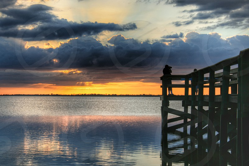 Photographer pier sunset water reflection water people clouds sky photo