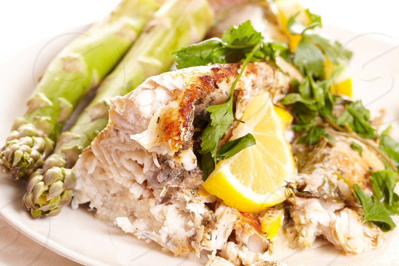 Fish dish with asparagus greens and lemon. photo