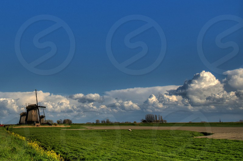 brown wind mill across green grass field under clear blue sky with white cumulus clouds photo