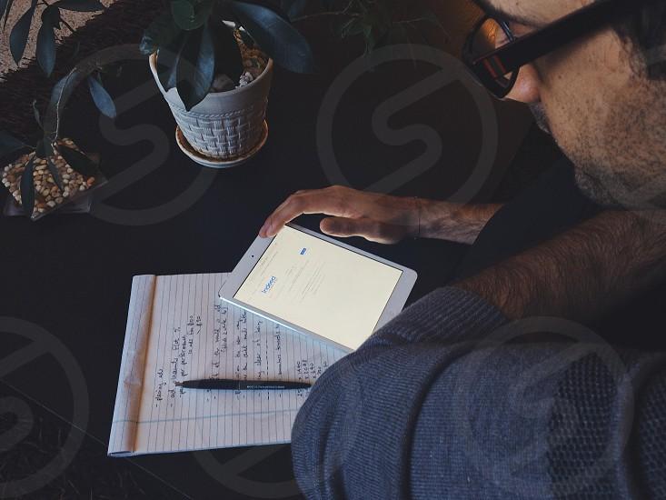 man sitting at black table using white ipad photo