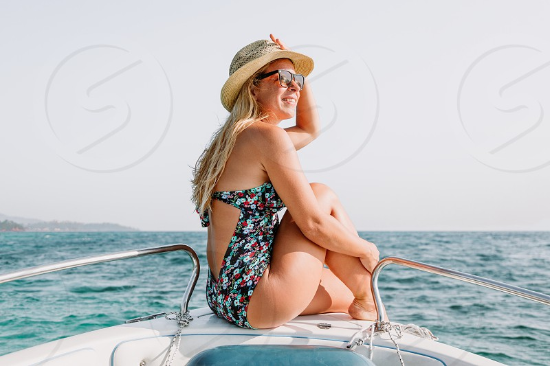 Young woman sitting on the bow of the boat enjoying the view at the sea photo