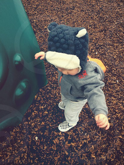 Baby learning to walk at park in winter wear  photo