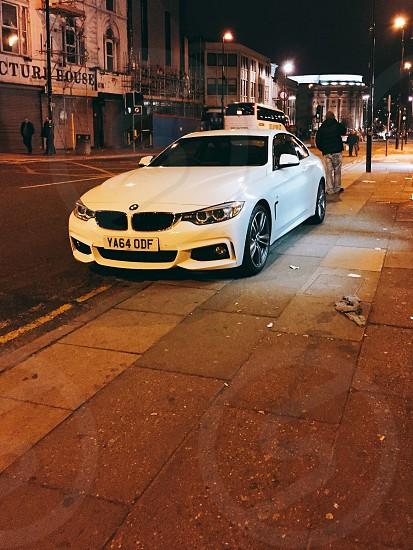 bmw car parking on sidewalk in nighttime photo