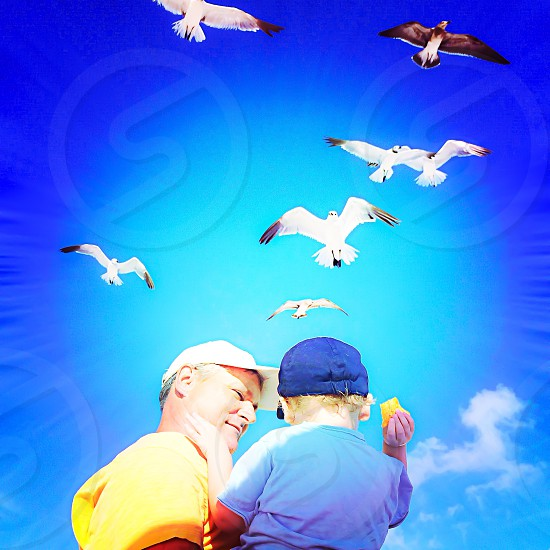 man carrying a boy with birds flying above image photo
