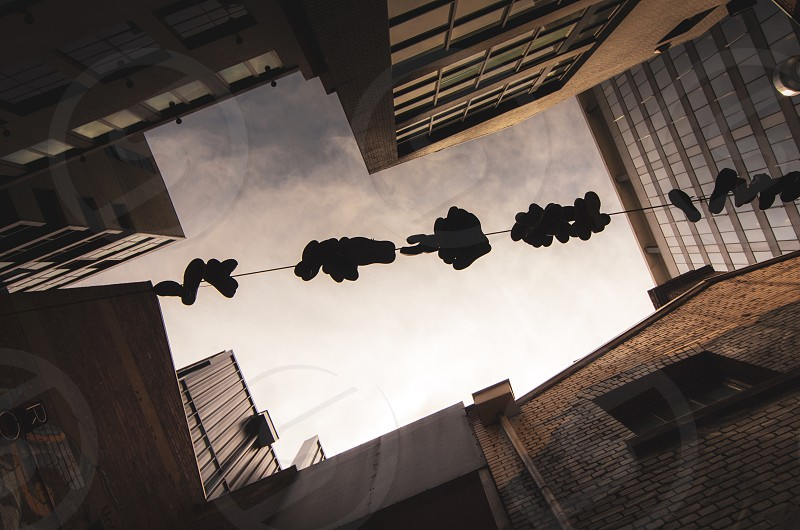 Street; sky; urban; buildings; angles; shoes on a wire photo