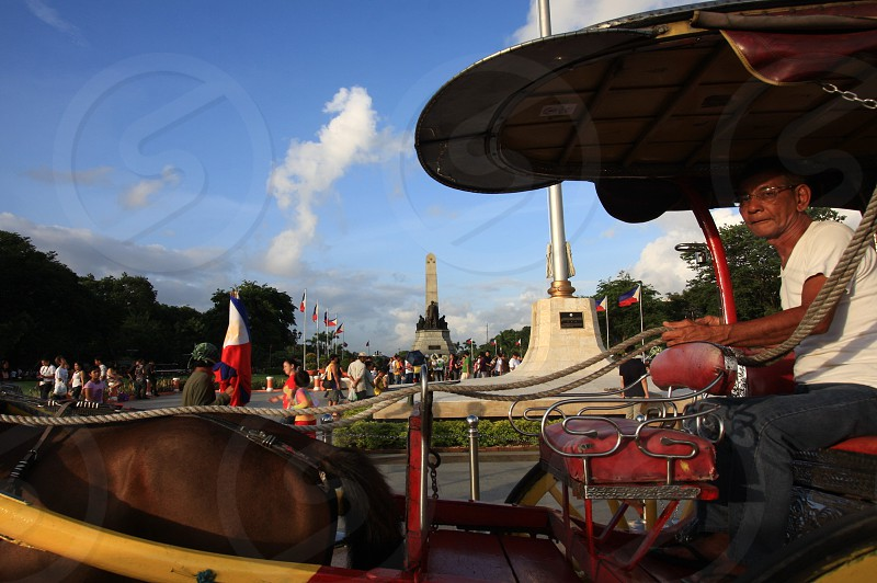 man in white crew-neck shirt riding a horse carriage photo
