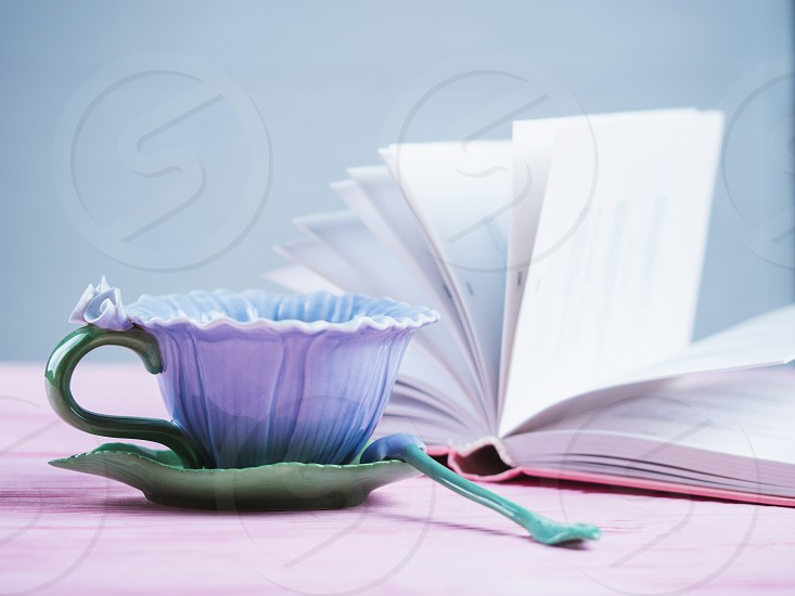 Romantic background with cup of tea and open book over light pink wooden table photo