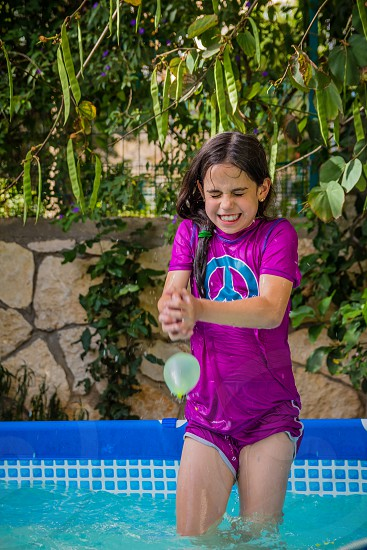 Young girl in a bathing suit try to catch water balloon in the pool in summer water balloon fight. photo
