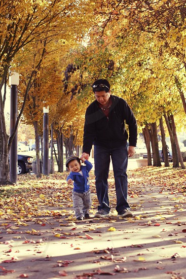 man holding child's hand while walking photo