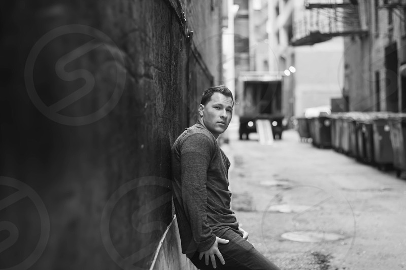 man wearing black long sleeve shirt and black jeans leaning on wall grayscale shot photo