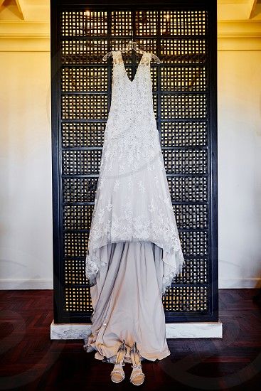 The front view of wedding dress hanging on the wooden weave partition with shoes on the floor during getting ready tungsten light in background. photo