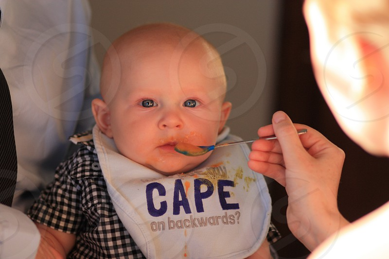 baby in black and white checked pattern shirt eating photo