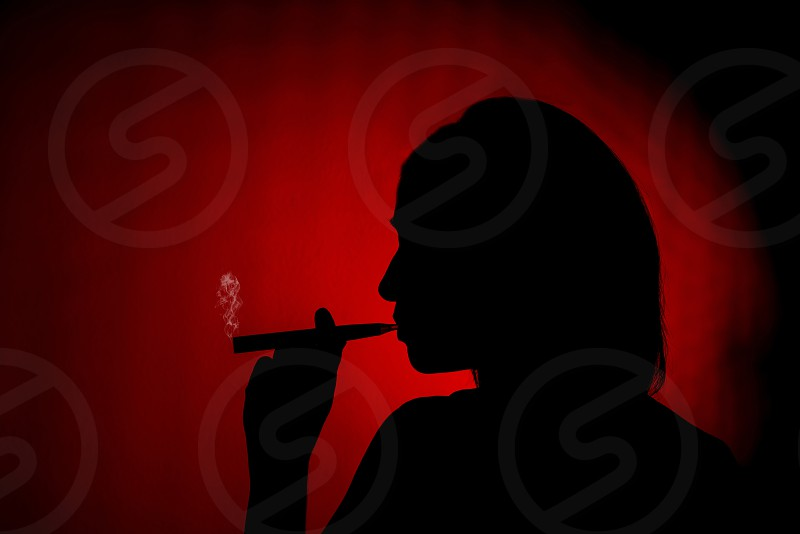 Silhouette of a female smoking an ecig on a red background photo