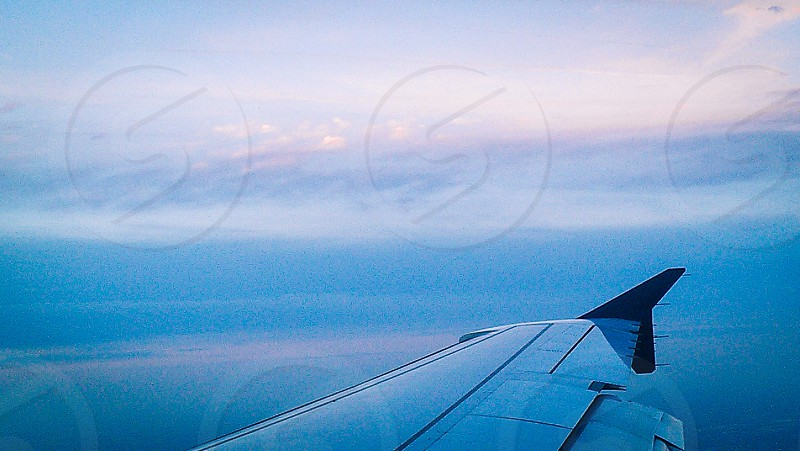 white clouds over airplane wing photo