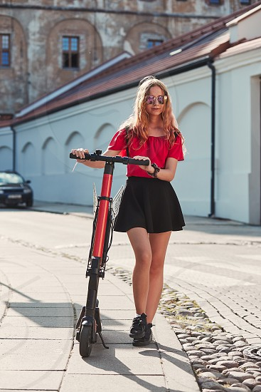Girl using electric scooter in the street in downtown rented by using service on smartphone. Candid people real moments authentic situations photo