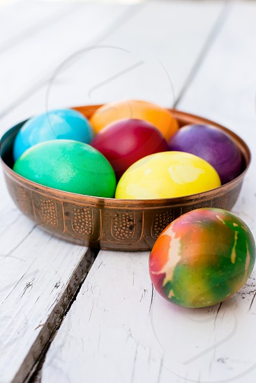 Brightly colored Easter eggs in a beautiful copper bowl photo