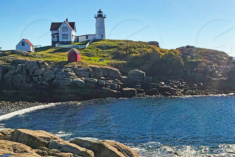 New England Lighthouse and buildings high on a hill near a rocky cove photo