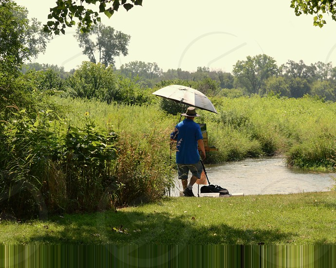 Plein air painter on location at a small river with easel and umbrella on a very sunny day. photo
