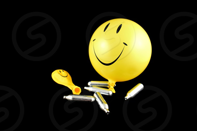 Laughing gas balloons. Happy emoji balloon stock images. Smiley inflatable balloon isolated on a black background. Laughing party balloon. Laughing gas bombs photo
