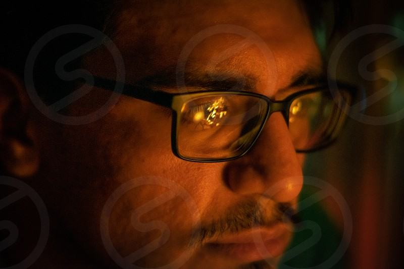 man staring into the fire reflecting on his glasses dark moody portrait photo
