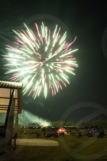Green fireworks burst over crowd photo